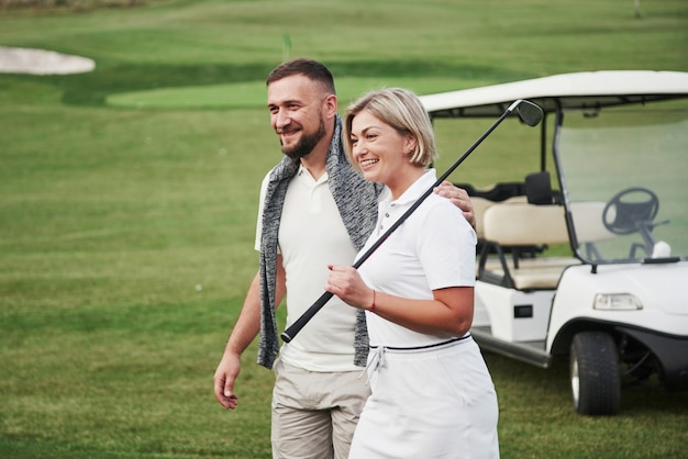 Dwóch golfistów, kobieta i mężczyzna, idą razem do następnej dziury. uczeń idzie ze swoim osobistym trenerem i jest zadowolony z sukcesów w sporcie