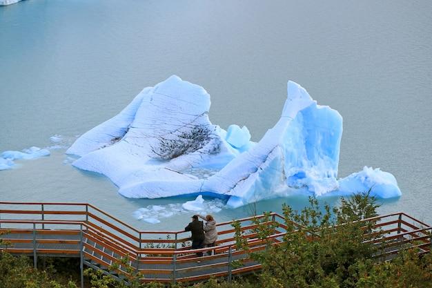Dwóch gości na balkonie widokowym przed ogromną górą lodową na jeziorze agentino, el calafate, argentyna