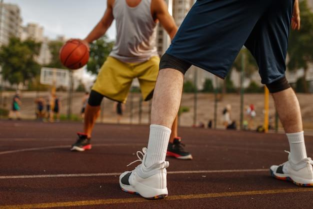Dwóch graczy na środku boiska do koszykówki na korcie zewnętrznym.