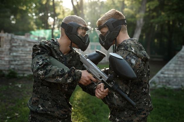 Dwóch graczy paintball z bronią pozuje na placu zabaw. sporty ekstremalne z bronią pneumatyczną i kulami lub markerami malarskimi, gra wojskowa w plenerze, taktyka walki