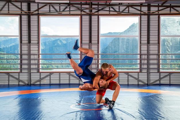 Dwóch grecko-rzymskich zapaśników w czerwonym i niebieskim mundurze rzucających uda na dywan zapaśniczy na siłowni.