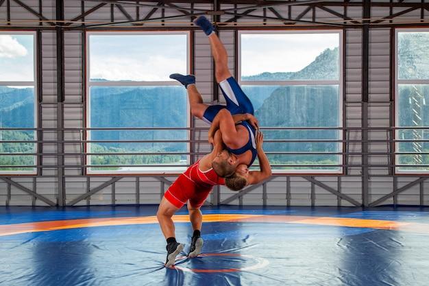 Dwóch grecko-rzymskich zapaśników w odzieży sportowej rzuca się przez klatkę piersiową na dywan zapaśniczy na siłowni