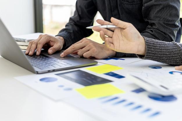 Dwóch handlowców pracuje razem nad przygotowaniem raportu sprzedaży firmy, który zostanie przedstawiony na comiesięcznym walnym zgromadzeniu z kierownictwem. spotkanie w celu dostosowania planów marketingowych w celu zwiększenia sprzedaży.
