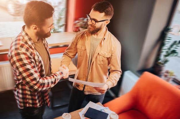 Dwóch hipsterów, którzy noszą codzienne ubrania, stojąc w małej kawiarni i ściskając ręce, jeden z nich trzyma w ręce dokument. oboje są zadowoleni ze współpracy.