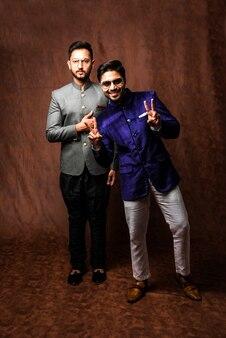 Dwóch indyjskich mężczyzn nosi etniczne lub tradycyjne ubrania, męskie modele mody z sherwani lub kurta pyjama, siedząc i pozując na krześle skrzydłowym lub sofie na brązowym tle grunge, selektywne skupienie