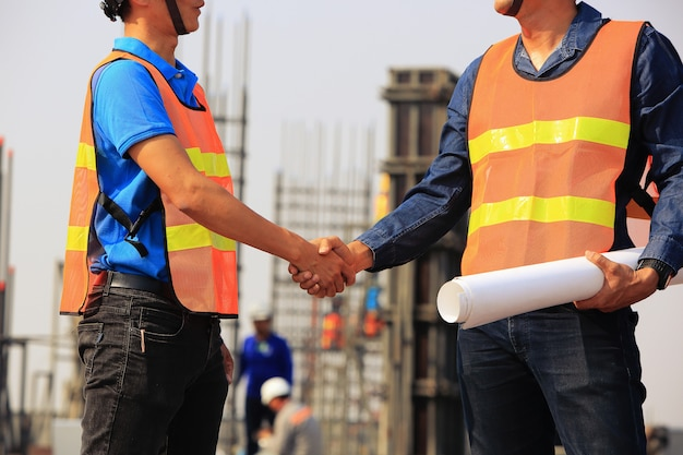 Dwóch inżynierów budowlanych uścisnąć dłoń na placu budowy