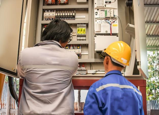 Dwóch inżynierów elektryka w inspekcji pracy urządzeń elektrycznych