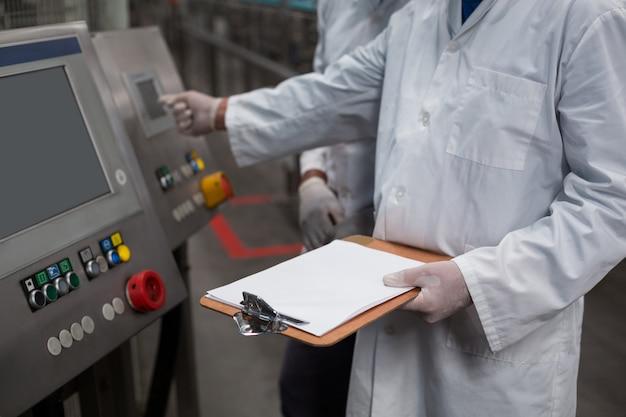 Dwóch inżynierów fabrycznych obsługujących maszynę w fabryce