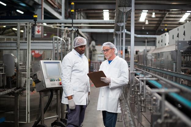 Dwóch inżynierów fabryki rozmawiających ze sobą