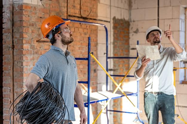 Dwóch inżynierów konstruktorów rozmawiających na placu budowy, inżynier wyjaśniający rysunek pracownikowi.