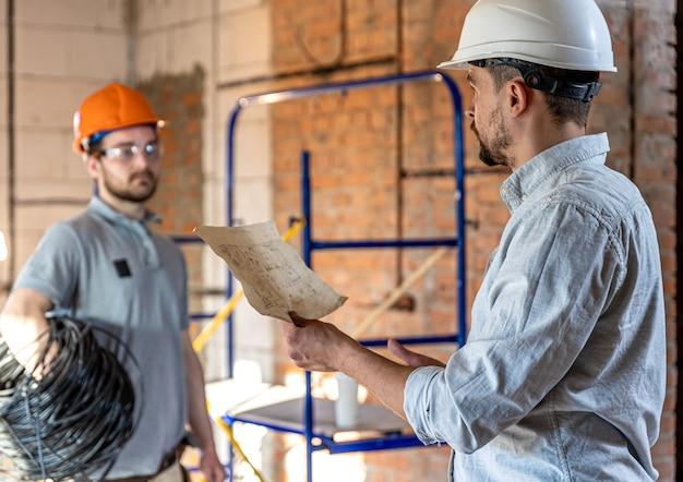 Dwóch inżynierów konstruktorów rozmawiających na placu budowy, inżynier wyjaśniający rysunek pracownikowi