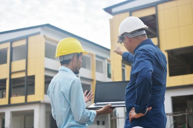 Dwóch inżynierów rozmawia na zewnątrz