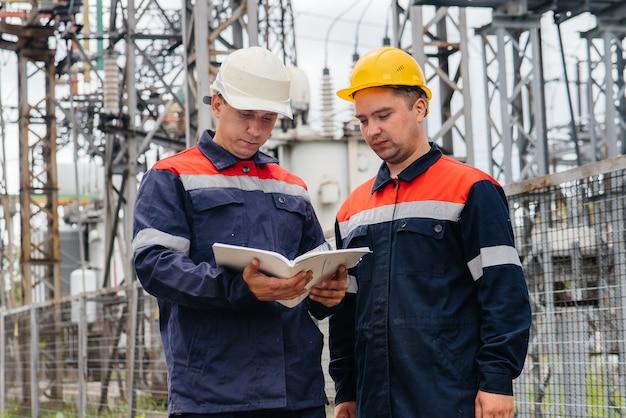 Dwóch inżynierów specjalizujących się w podstacjach elektrycznych dokonuje przeglądu nowoczesnych urządzeń wysokiego napięcia. energia. przemysł.