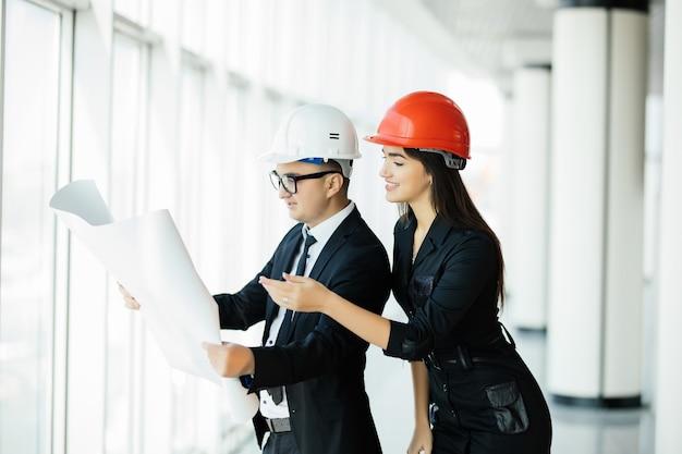 Dwóch inżynierów stoi w pobliżu panoramicznego okna i wskazuje plan budowy