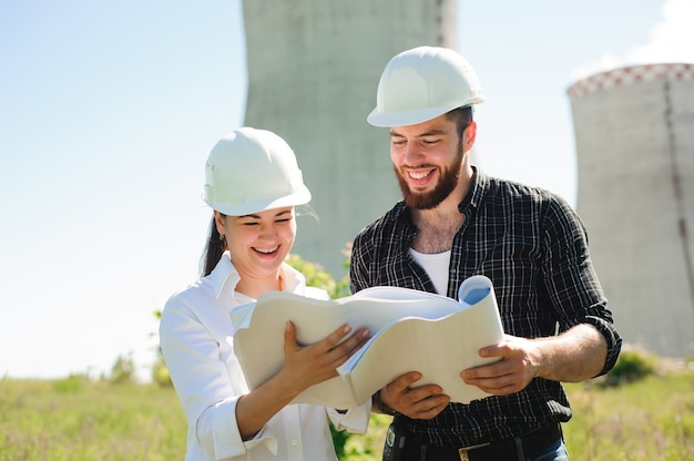 Dwóch inżynierów stojących przy stacji elektrycznej, omawiających plan.