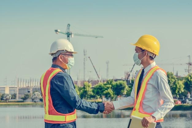 Dwóch inżynierów uścisnąć dłoń projekt sukcesu umowy na budowę placu budowy