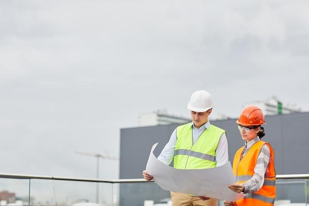Dwóch inżynierów w odblaskowych ubraniach stoi na zewnątrz i razem badają projekt nowego budynku