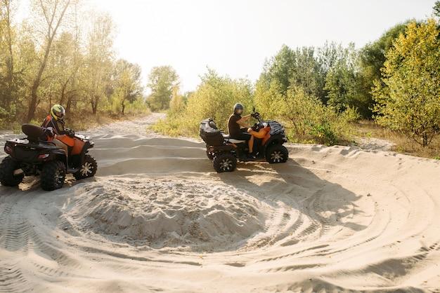 Dwóch jeźdźców atv w kaskach biegających po piasku, offroad w lesie. jazda quadem, sporty ekstremalne i podróże, przygoda na quadach