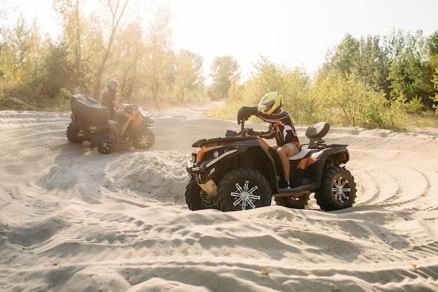 Dwóch jeźdźców atv w kaskach jeździ w kółko po piasku, offroad w lesie. jazda quadem, sporty ekstremalne i podróże, letnia przygoda na quadach