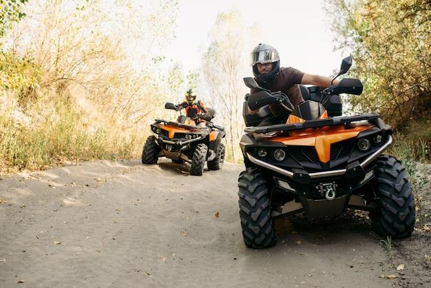 Dwóch jeźdźców quadów w kaskach podróżuje po lesie, widok z przodu. jazda na quadach, sporty ekstremalne i podróże, przygoda na quadach