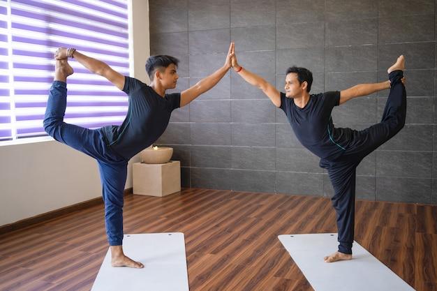 Dwóch joginów robi pana tancerzy stanowią w siłowni