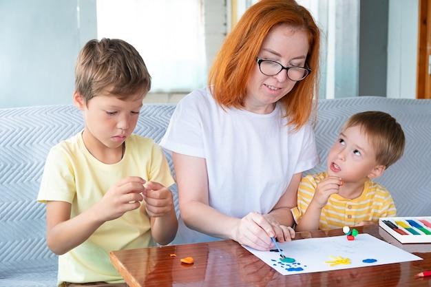 Dwóch kaukaskich chłopców i rudowłosa kobieta w okularach bawią się kolorową plasteliną w przedszkolu lub w domu