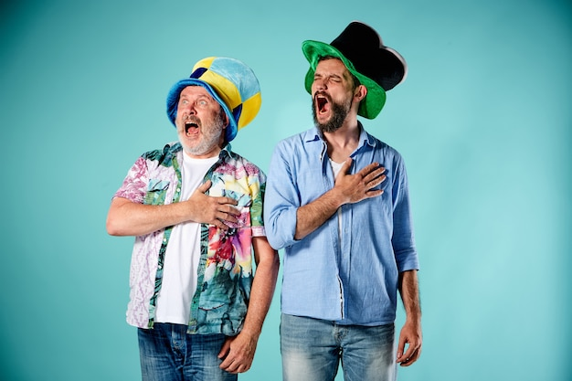 Dwóch kibiców śpiewa hymn narodowy na niebiesko