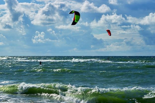 Dwóch kitesurferów szybuje po morzu przy słonecznej, wietrznej pogodzie
