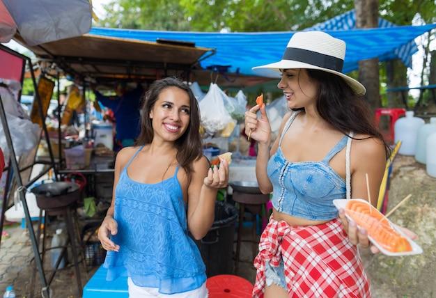 Dwóch kobiet turystów jedzą świeże owoce happy smiling walking street