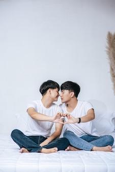 Dwóch kochających się młodych mężczyzn patrzy na siebie i robi dłoń z symbolem miłości.