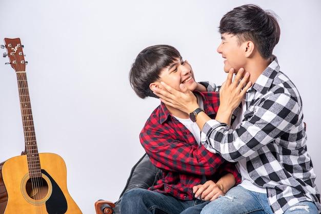 Dwóch kochających się młodych mężczyzn siedzących na policzku na krześle, z gitarą obok
