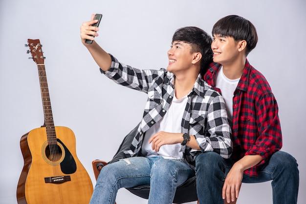 Dwóch kochających się młodych mężczyzn siedzi na krześle i robi selfie ze smartfona.