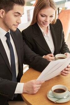 Dwóch kolegów biznesowych omawianie dokumentów podczas śniadania w kawiarni