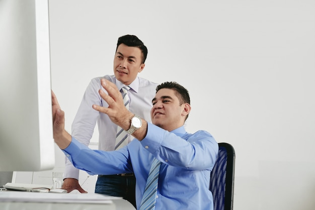 Dwóch kolegów burzy mózgów w biurze, patrząc na ekran komputera