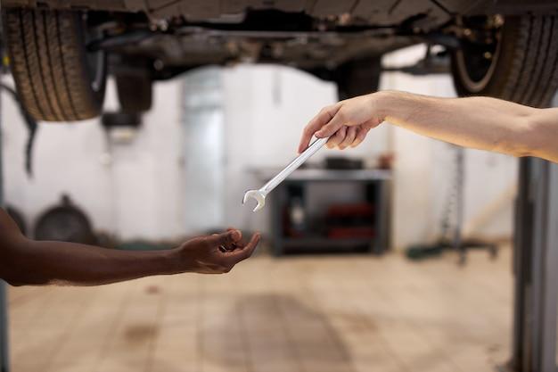 Dwóch kolegów mechaników samochodowych daje sobie narzędzia