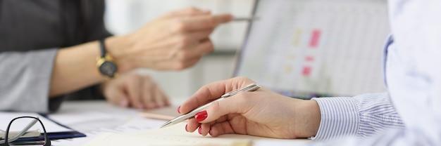 Dwóch kolegów omawia komercyjne wskaźniki biznesu na małym i średnim tablecie