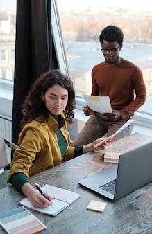 Dwóch kolegów posługujących się w pracy dokumentami i komputerem przygotowuje się do prezentacji w biurze
