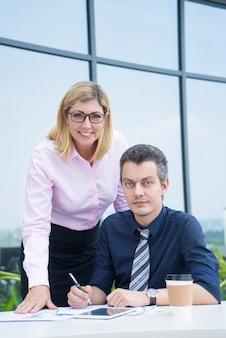 Dwóch kolegów pracujących na papierze w kawiarni na świeżym powietrzu i pozowanie.