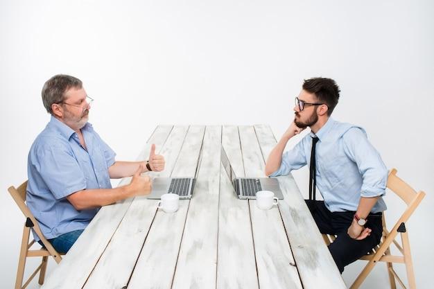 Dwóch kolegów pracujących razem w biurze na białym tle. obaj patrzą na ekrany komputerów. jeden człowiek otrzymuje dobre wieści, inni złe wieści