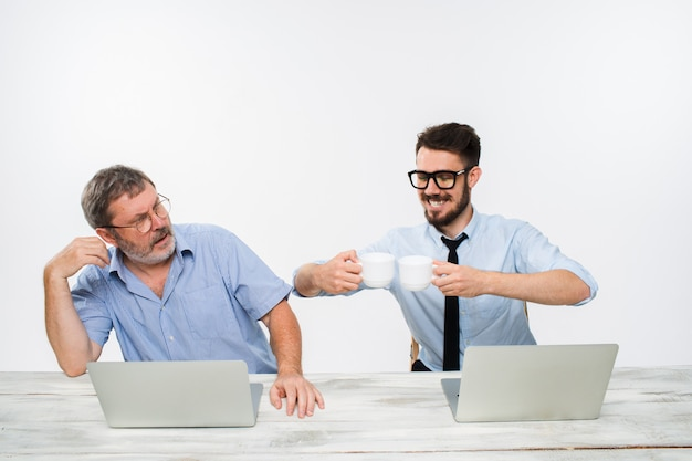 Dwóch kolegów pracujących razem w biurze na białym tle