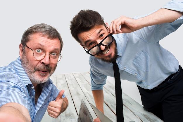 Dwóch kolegów robiących im zdjęcie siedzi w biurze