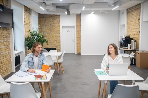 Dwóch kolegów siedzących przy stołach w biurze