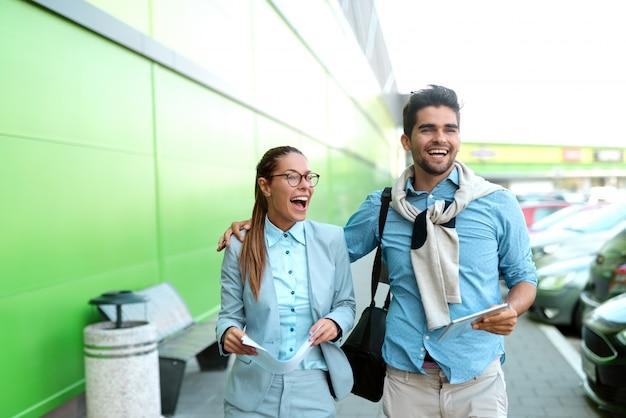 Dwóch kolegów spacerujących po ulicy po pracy. kobieta trzyma papierkową robotę, podczas gdy mężczyzna trzyma tablet i przytula ją.