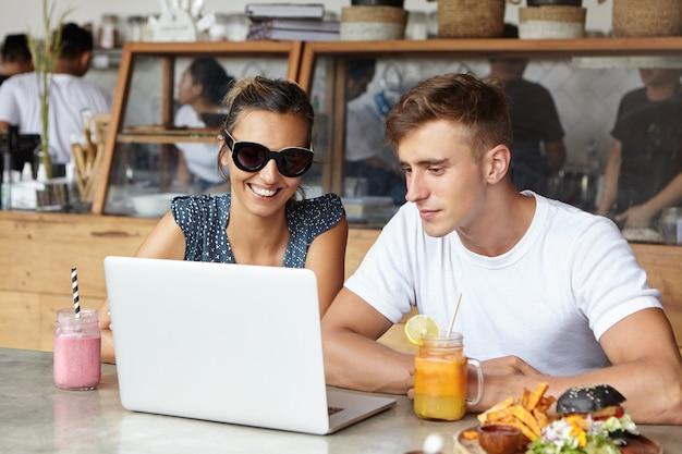 Dwóch kolegów spędzających razem miło czas podczas lunchu w kawiarni po pracy przy laptopie. stylowa kobieta oglądająca zdjęcia za pośrednictwem mediów społecznościowych