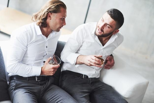 Dwóch kolegów z drużyny rozmawia w przerwie i pije whisky