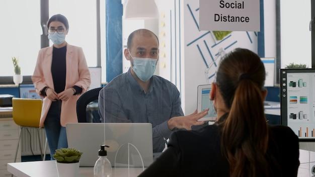 Dwóch kolegów z maskami na twarzy pracujących nad projektem marketingowym przy użyciu komputera typu tablet, siedząc w biurze firmy. zespół biznesowy zachowuje dystans społeczny, aby uniknąć zakażenia koronawirusem