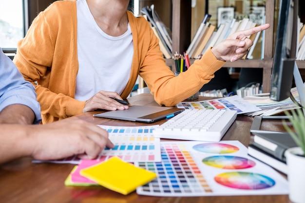 Dwóch kreatywnych grafików pracujących nad wyborem kolorów i próbek, rysowanie na tablecie graficznym