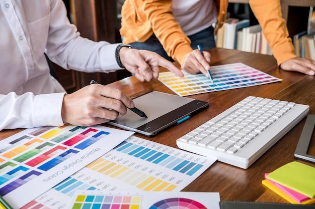 Dwóch kreatywnych grafików pracujących nad wyborem kolorów i rysowaniem na tablecie graficznym