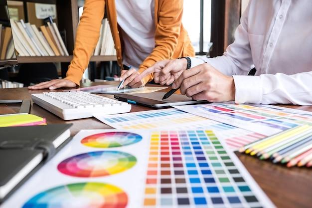 Dwóch kreatywnych grafików pracujących nad wyborem koloru i próbkami kolorów
