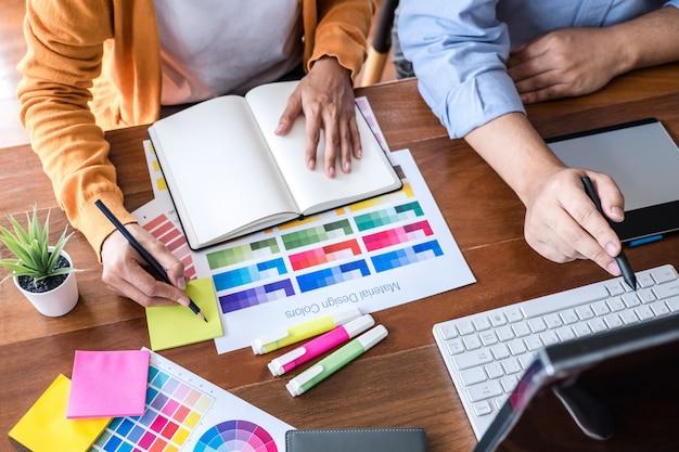 Dwóch kreatywnych grafików pracujących przy wyborze kolorów i próbkach kolorów, rysujących na tablecie graficznym